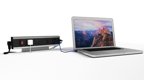 Modular PDCM power outlet with sockets, ethernet and USB port and loaptop adapters on desk powering laptop