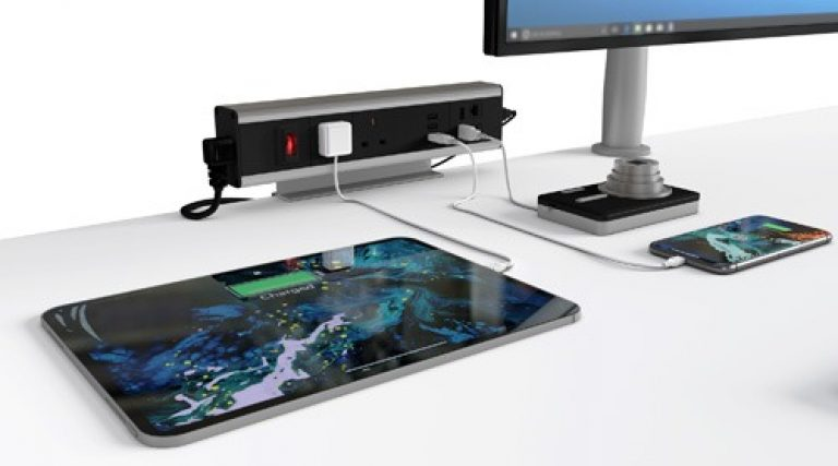 Modular PDCM power outlet with sockets, ethernet and USB port and loaptop adapters on desk charging camera, phone and tablet