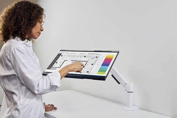 Person demonstrating the use of the Flyt touchscreen monitor arm
