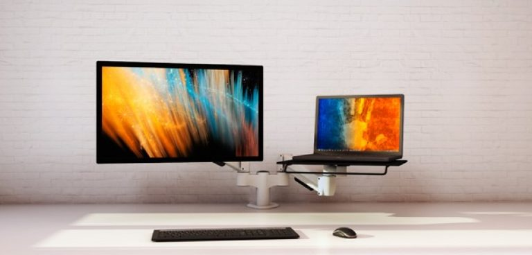 White double SpaceArm monitor arm with one monitor screen and one laptop
