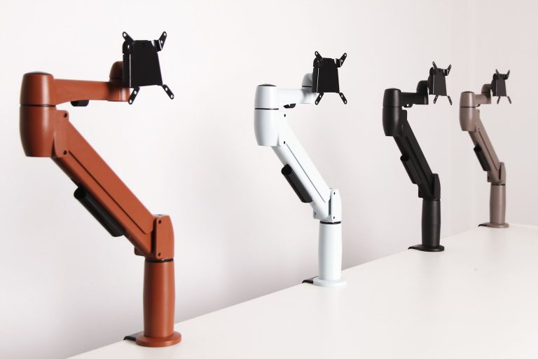 Three different coloured SpaceArm monitor arms, white, black and orange