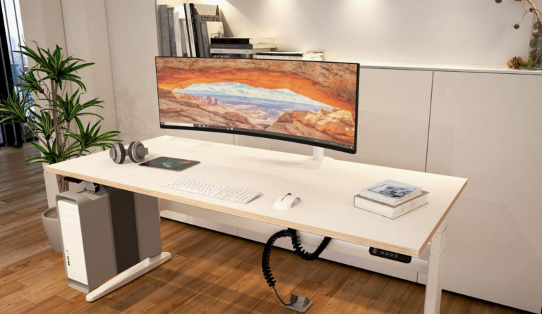 Sit-stand desk with SpaceArm monitor arm holding large, curved monitor